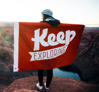 Girl standing on a mountain with a keep exploring flag